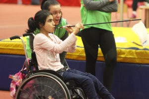 Girl in a wheelchair plays with a blowpipe, assisted by an adult wearing a green bib